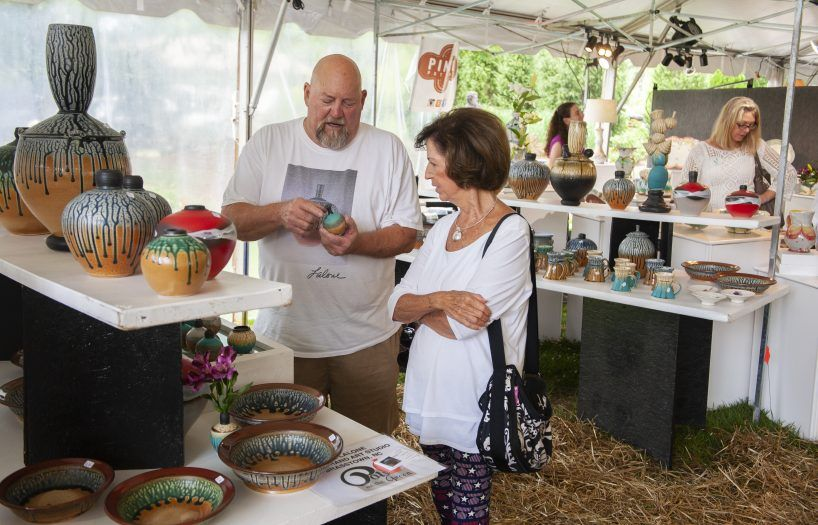 couple admiring a piece of pottery in jackson county