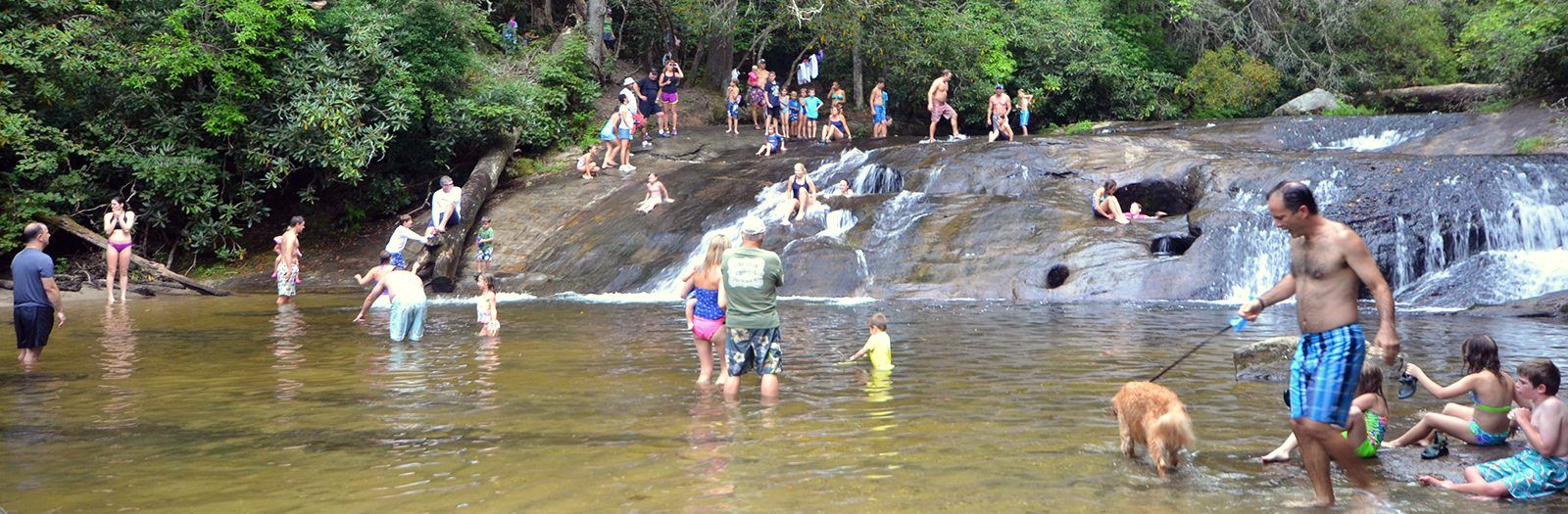families playing and sliding down the waterfall of sliding rock in jackson county