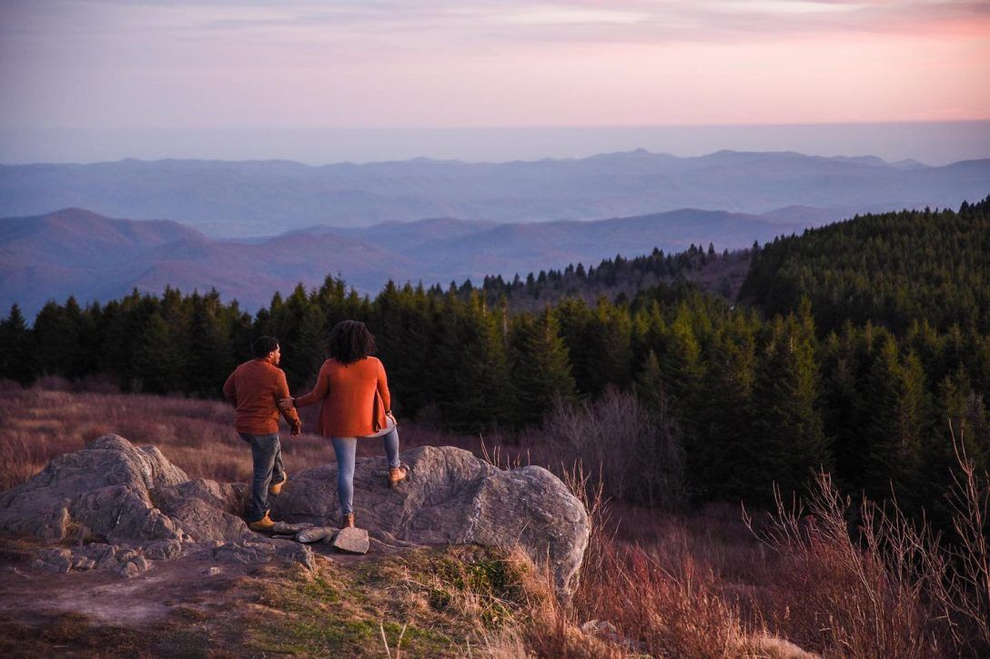 Couple standing atop of Black Balsam Knob, enjoying a sunset view.