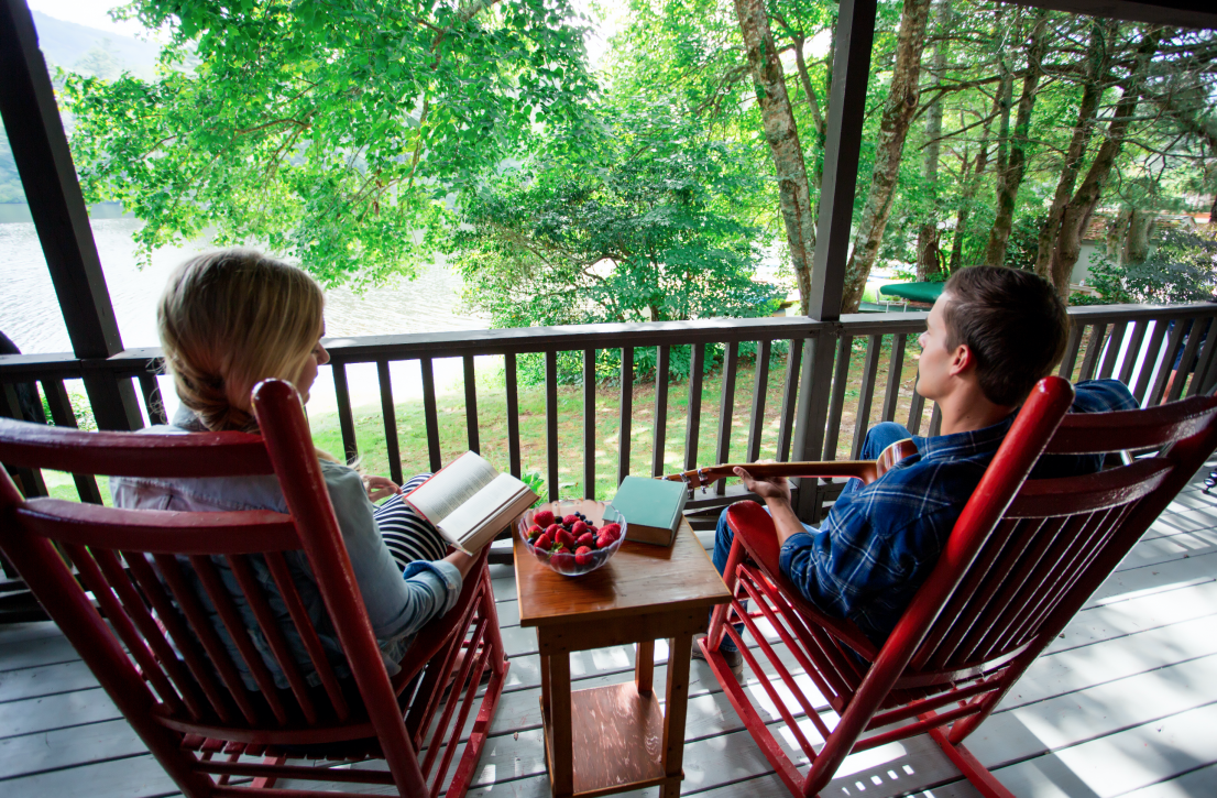 Man and woman enjoying spring day on the porch of a cabin.