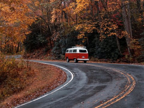 VW Bus winding on mountain road during fall.